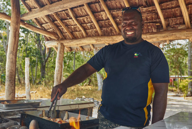 A tour guide cooking Lunch on the Lelepa Island day tour.