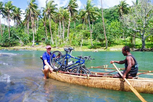 Taking bikes across a river on a ecotours bike trip near Port Vila